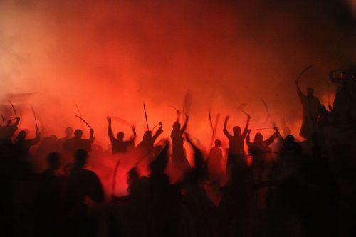 men brandishing weapons in lurid firelight