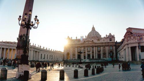 sun rising behind Vatican church cathedral